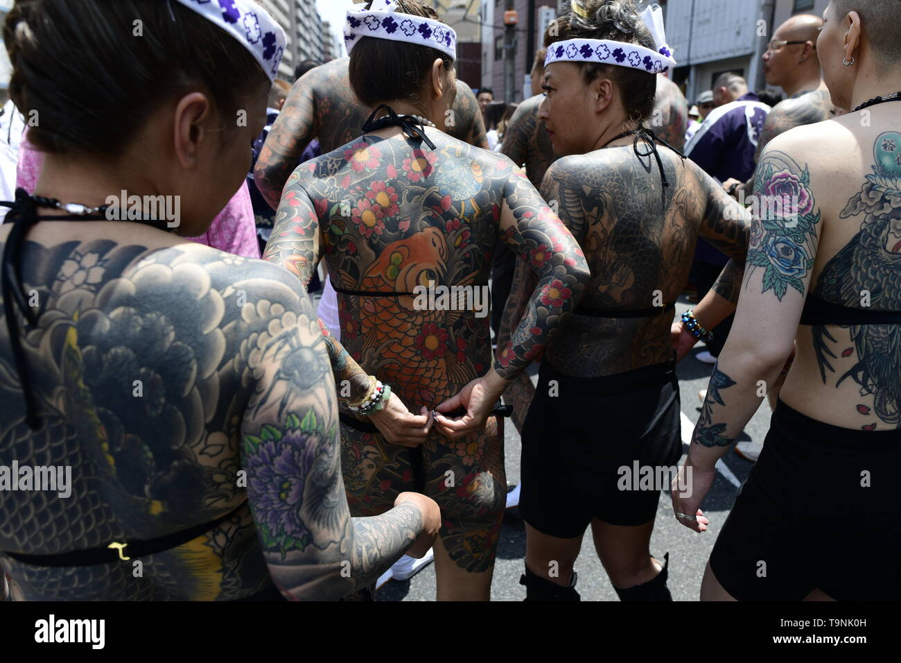 "TOKYO, JAPAN - MAY 18: Heavily tattooed Japanese women chat in the street as they wait for the portable shrine in the street of Asakusa during ""Sanja Matsuri"" on May 18, 2019 in Tokyo, Japan. A boisterous traditional mikoshi (portable shrine) is carried in the streets of Asakusa to bring goodluck, blessings and prosperity to the area and its inhabitants. (Photo: Richard Atrero de Guzman/ AFLO) Stock Photo"