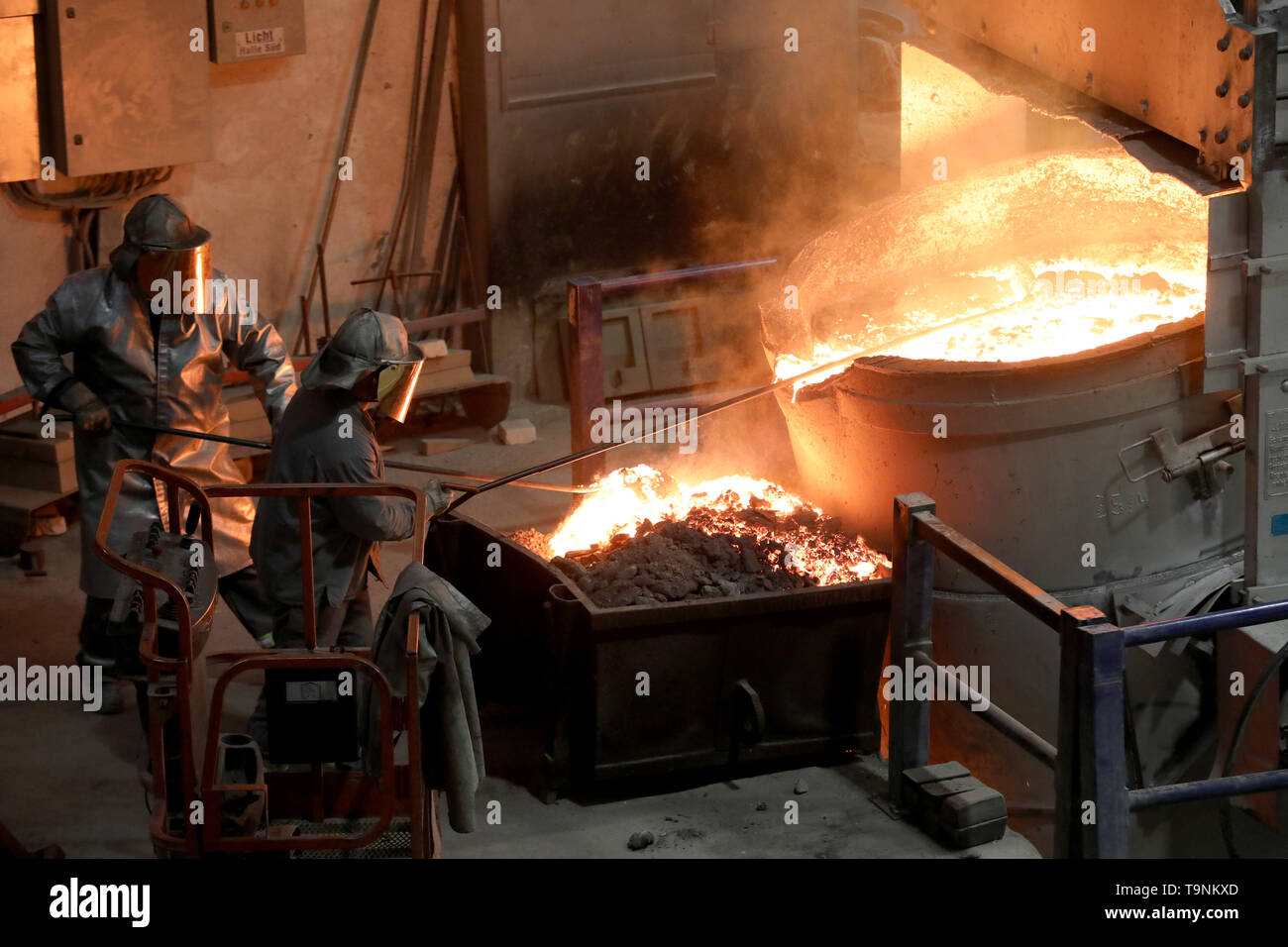 08 May 2019, Mecklenburg-Western Pomerania, Waren: In the foundry of Mecklenburger Metallguss GmbH MMG the slag is removed from the aluminium bronze before casting a large ship propeller. A total of 165 tons of material with a temperature of about 1,170 degrees is poured into a mold. The propeller for a large Korean container freighter will later have a diameter of 10.40 meters and weigh 117 tons. Less than a year after its transition to independence, MMG sees itself on the upswing again. Sales of 50 million euros are expected for 2019, about ten million euros more than in 2018. Photo: Bernd W - Stock Image