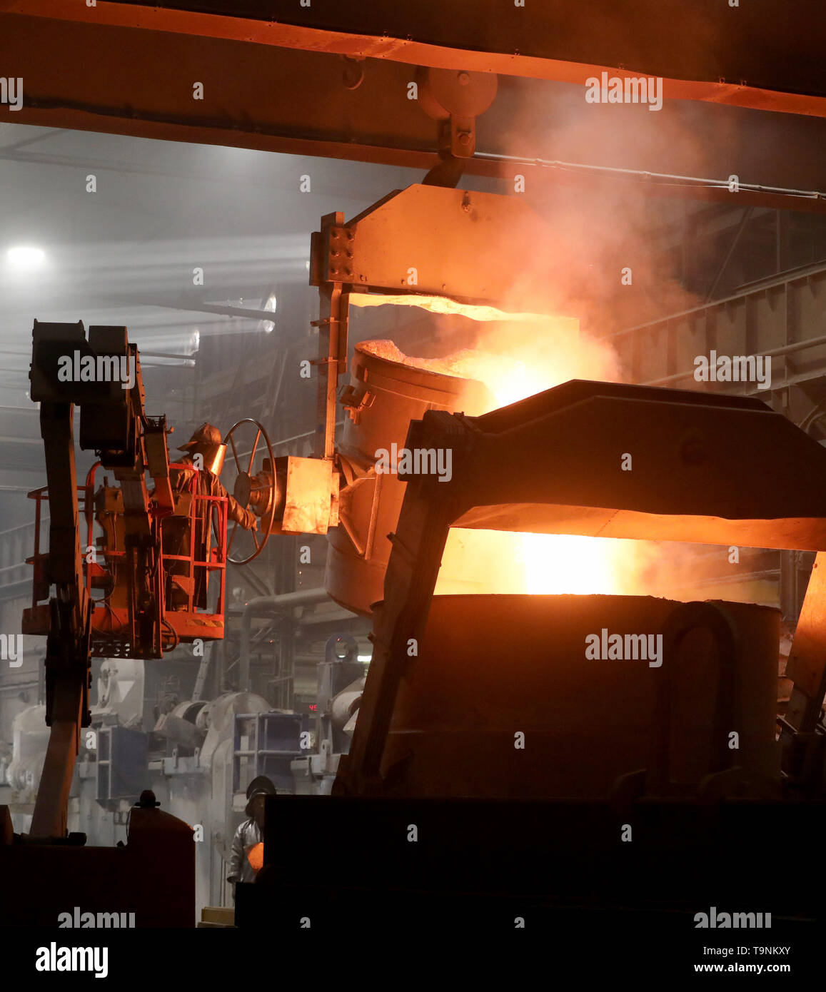08 May 2019, Mecklenburg-Western Pomerania, Waren: In the foundry of Mecklenburger Metallguss GmbH MMG, a crane ladle is filled with 80 tons of aluminium bronze. Together with another 85 tons directly from a furnace, the approx. 1,170 degree hot material is then poured into a huge mould for a ship's propeller. The propeller for a large Korean container freighter will later have a diameter of 10.40 meters and weigh 117 tons. Less than a year after its transition to independence, MMG sees itself on the upswing again. Sales of 50 million euros are expected for 2019, about ten million euros more t - Stock Image