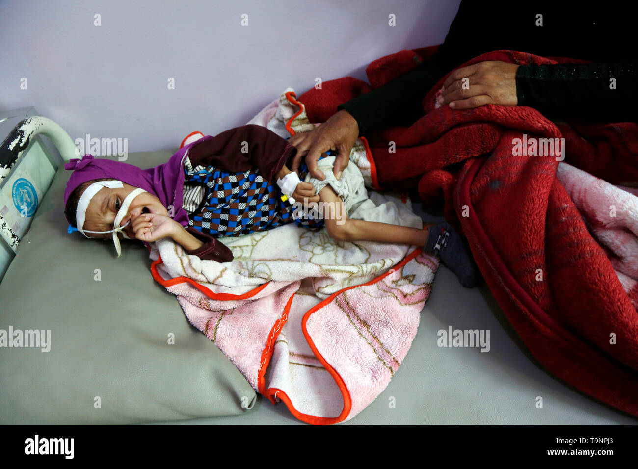 (190520) -- SANAA, May 20, 2019 (Xinhua) -- A mother sits with her malnourished daughter who lies on a bed while receiving treatment at a malnutrition care-center in Sanaa, Yemen, on May 19, 2019. With 360,000 children suffering from severe acute malnutrition and 2.5 million - or half of all children under the age of five - stunted, the country is spiralling perilously close to the brink, Executive Director of the United Nations Children's Fund  (UNICEF) Henrietta Fore warned. (Xinhua/Mohammed Mohammed) - Stock Image