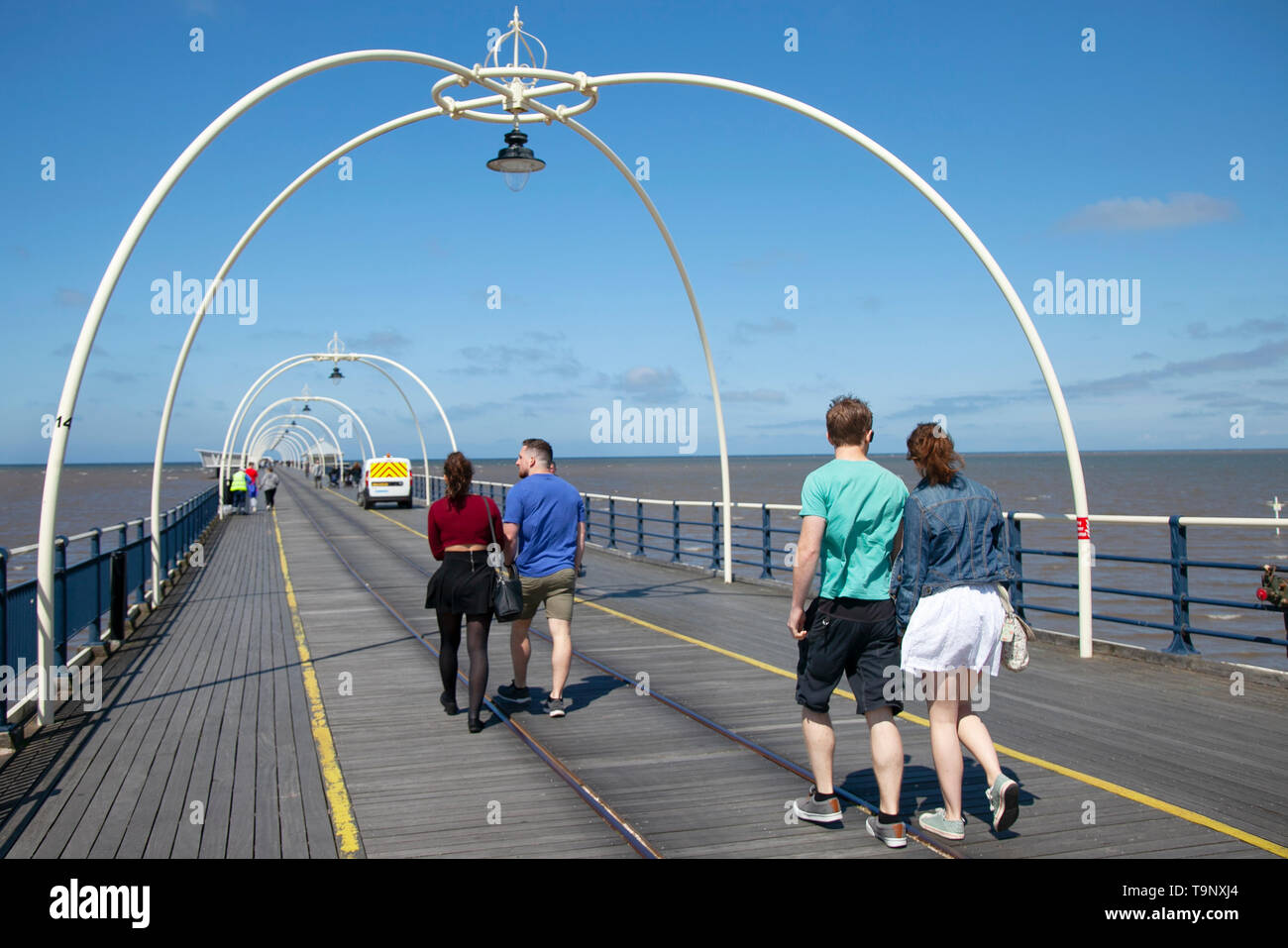 Southport, Merseyside. 20th May 2019. UK Weather. Bright sunny start to the day as local residents take a stroll on the restored Venetian Pier. Shirt sleeves & shorts are the order of the day as temperatures warm up in the north-west. Credit: MediaWorldImages/Alamy Live News - Stock Image