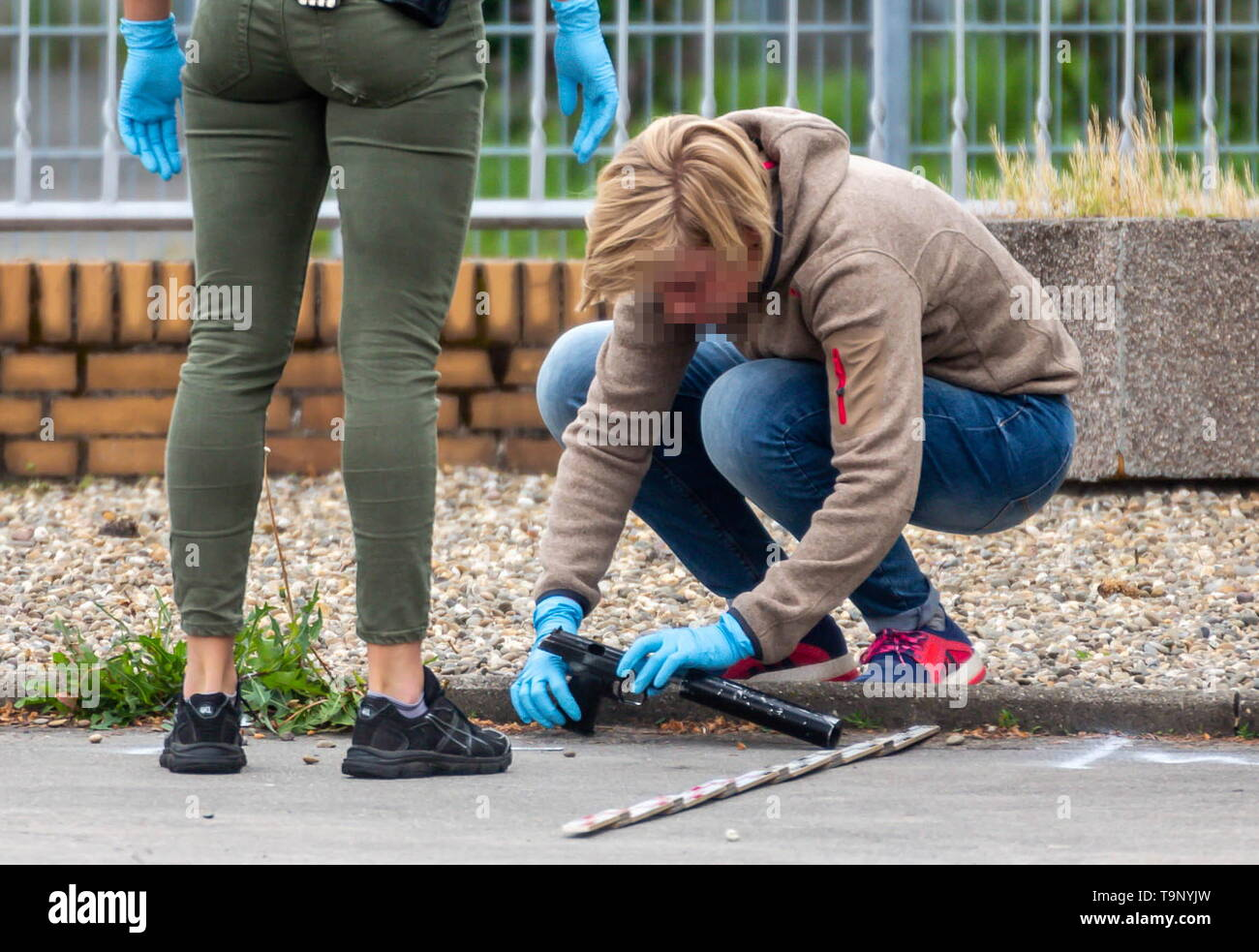 20 May 2019, Hessen, Flörsheim: Police officers secure the suspected murder weapon with which a 34-year-old man was shot after a dispute and became life-threatening. According to initial investigations, the men got into a dispute around 6.30 a.m. in the morning. A police spokesman said that a 54-year-old is said to have shot the younger one at least once. ATTENTION: The police officer was made unrecognisable for reasons of personality rights. Photo: Stenzel/Wiesbaden112.de/dpa - Stock Image