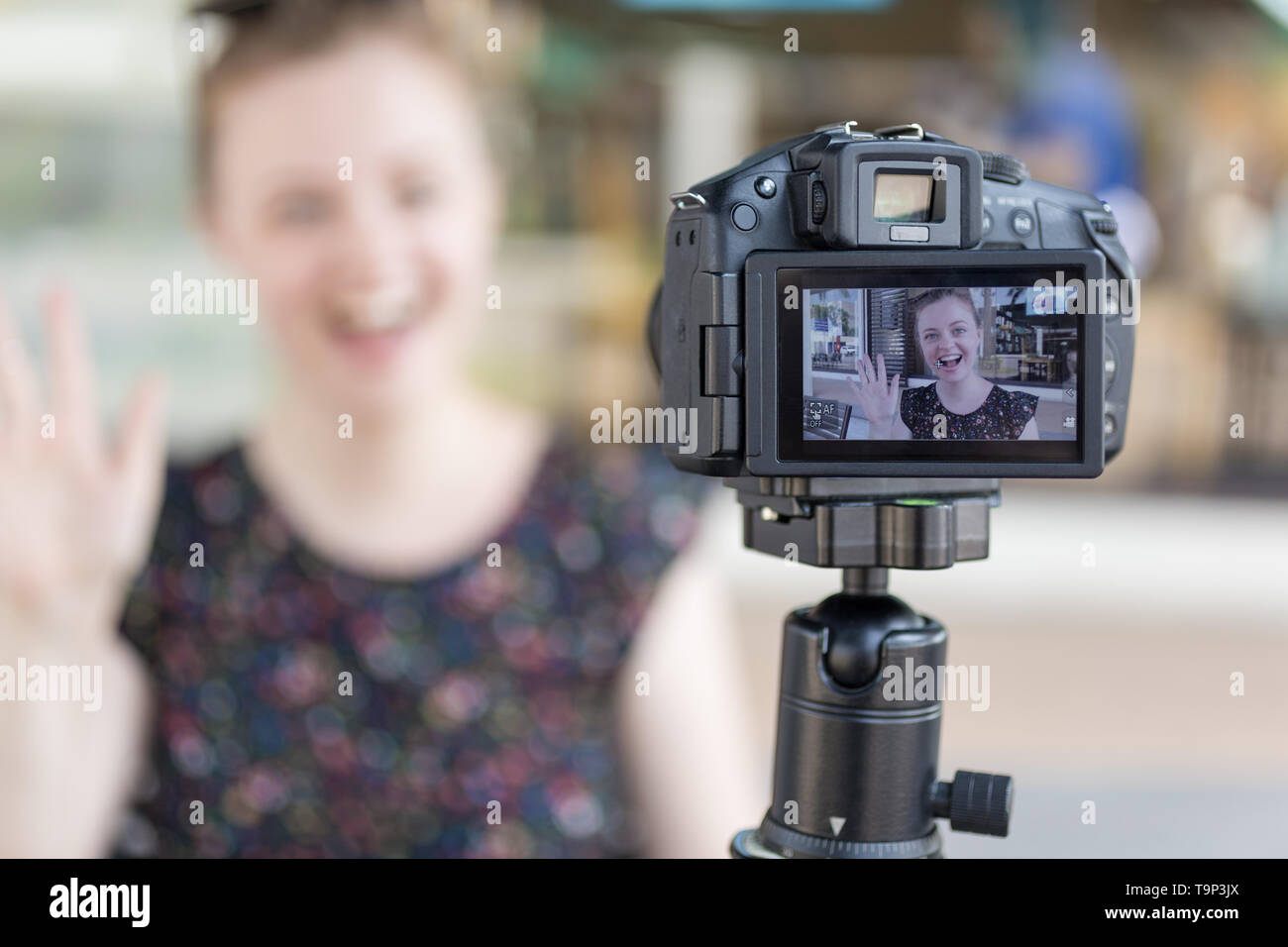 A caucasian young girl making a video blog (vlog) behind the camera Stock Photo