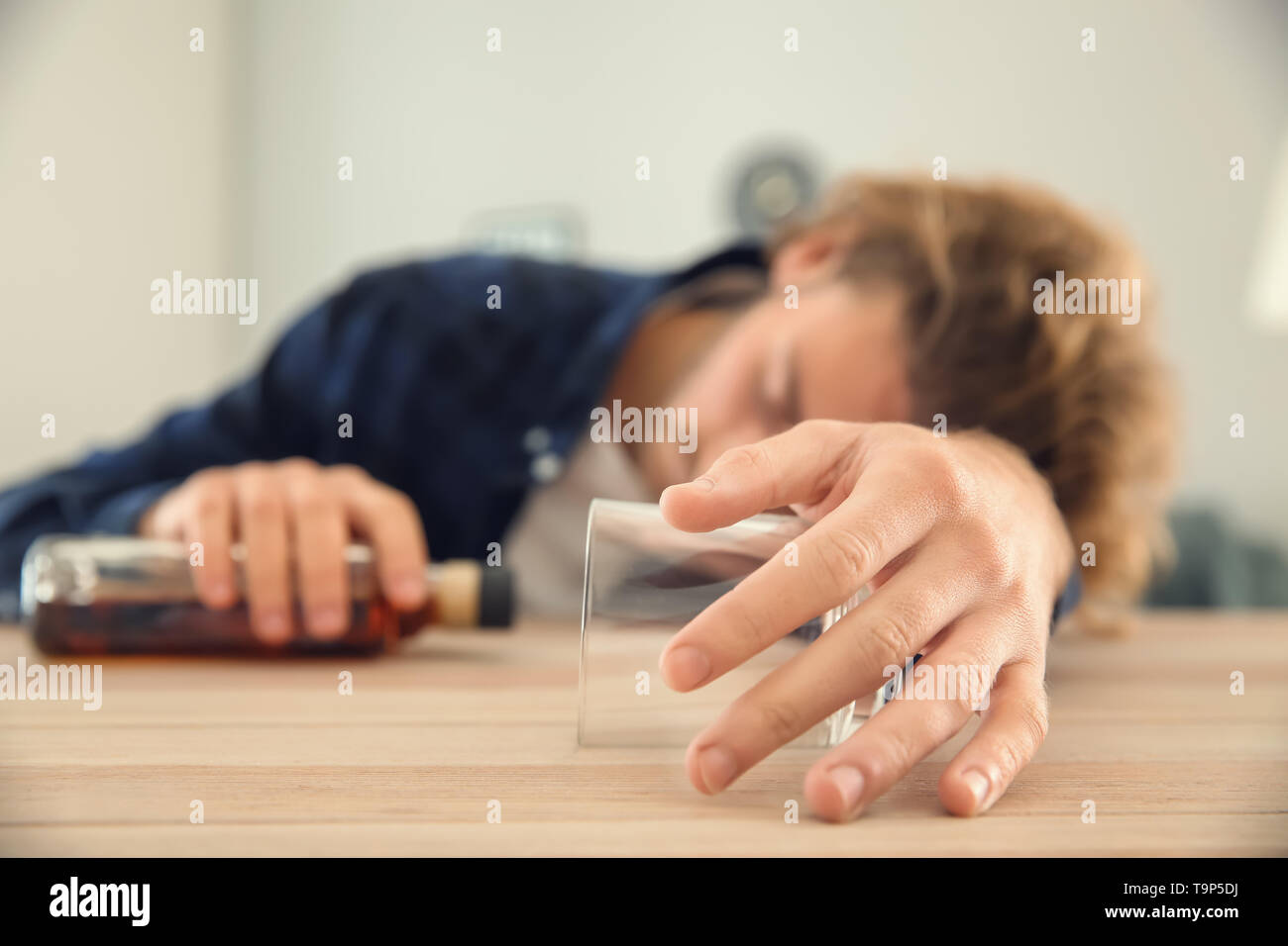Unconscious drunk man with bottle and empty glass at table. Alcoholism concept Stock Photo