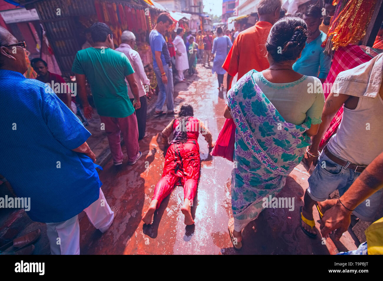 Bengalee, year end,female worshiper,stretching,on Kali temple,hot pavement, under, mid-day,Sun,for ,piety,Kalighat,Kolkata,India. Stock Photo