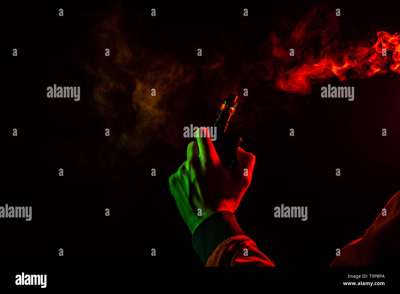 A man body part arm and hand view with green light in a orange hoodie smokes a vape and exhales a red smoke on a black isolated background. Harm to hu - Stock Image