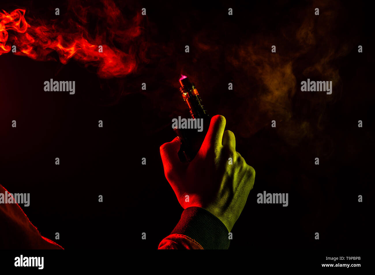 A man body part arm and hand view with yellow light in a orange hoodie smokes a vape and exhales a red smoke on a black isolated background. Harm to h - Stock Image