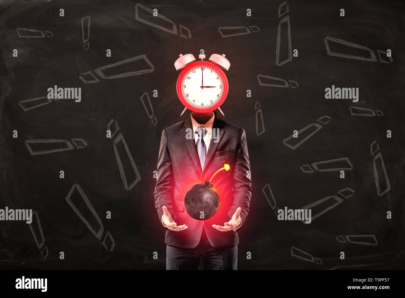 Businessman with clock instead of head holding ball bomb with fuse on black background with exclamation sign pattern - Stock Image
