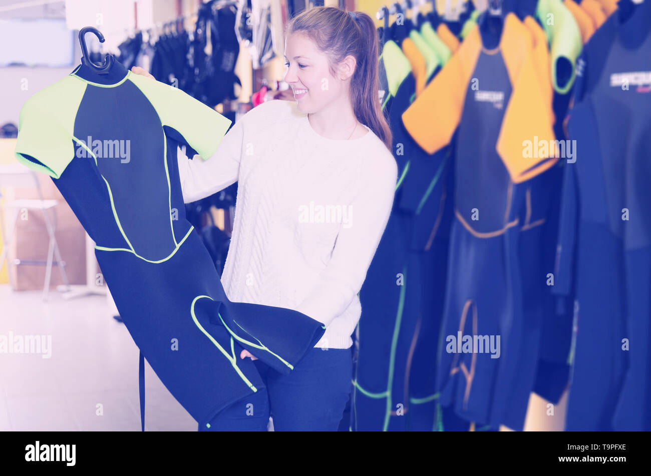 woman is satisfied of new costumes for diving in the store. - Stock Image