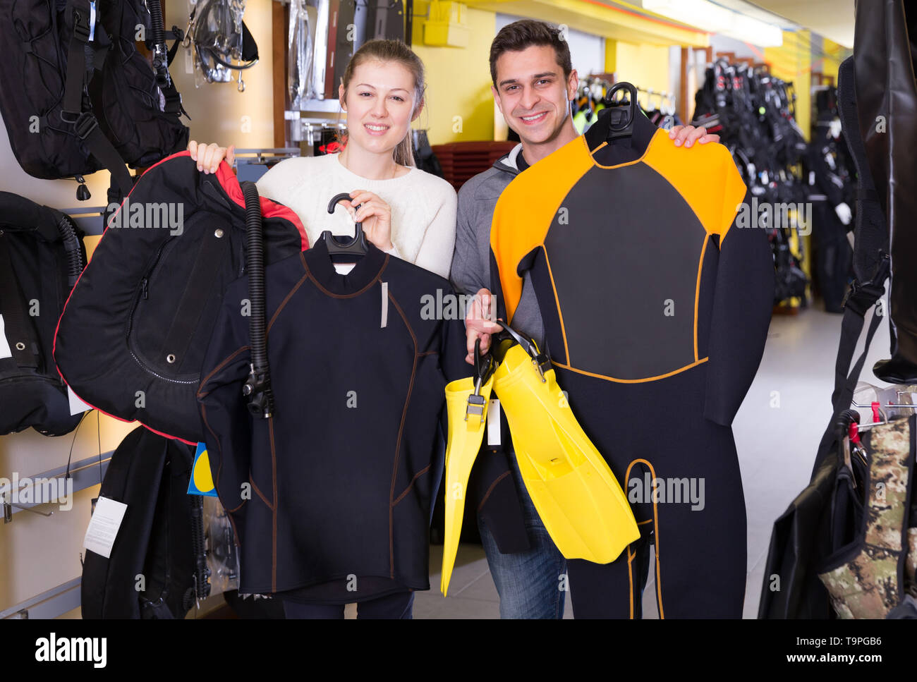 Sporty woman and man are satisfied of full set of diving equipment in the store. - Stock Image