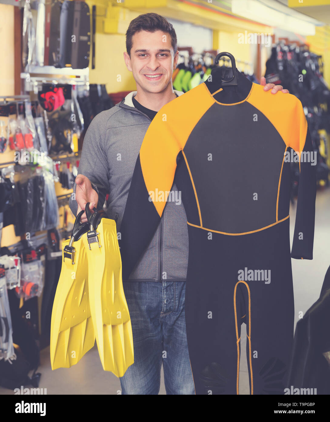 Sporty man is satisfied of new costumes for diving and flippers in the store - Stock Image