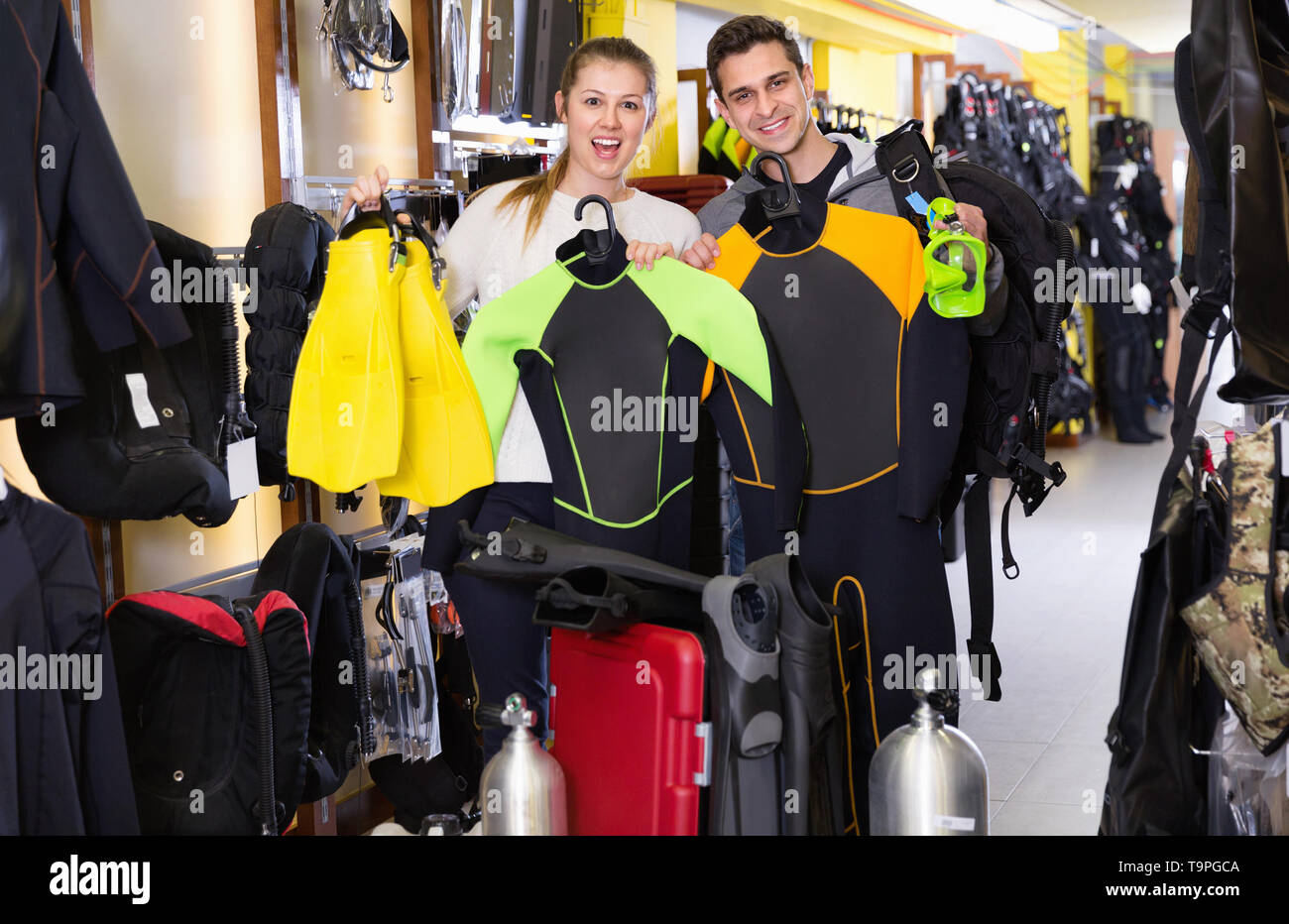 Glad cheerful positive  man and woman are standing with modern diving equipment in the store. - Stock Image