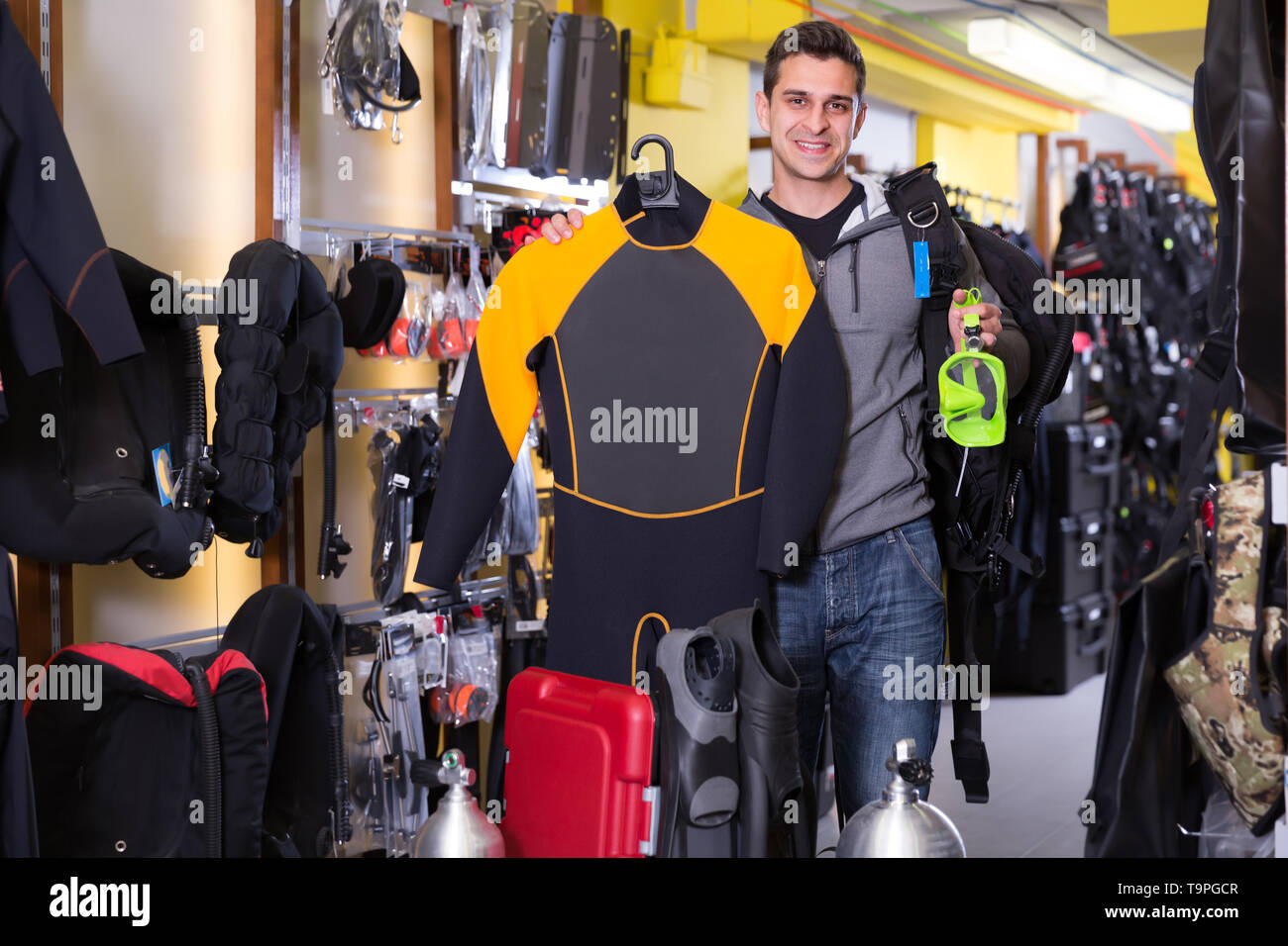 Sporty man is satisfied of full set of diving equipment in the store - Stock Image