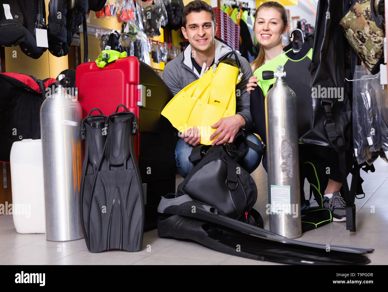 Glad  positive smiling man and woman are standing with modern diving equipment in the store. - Stock Image