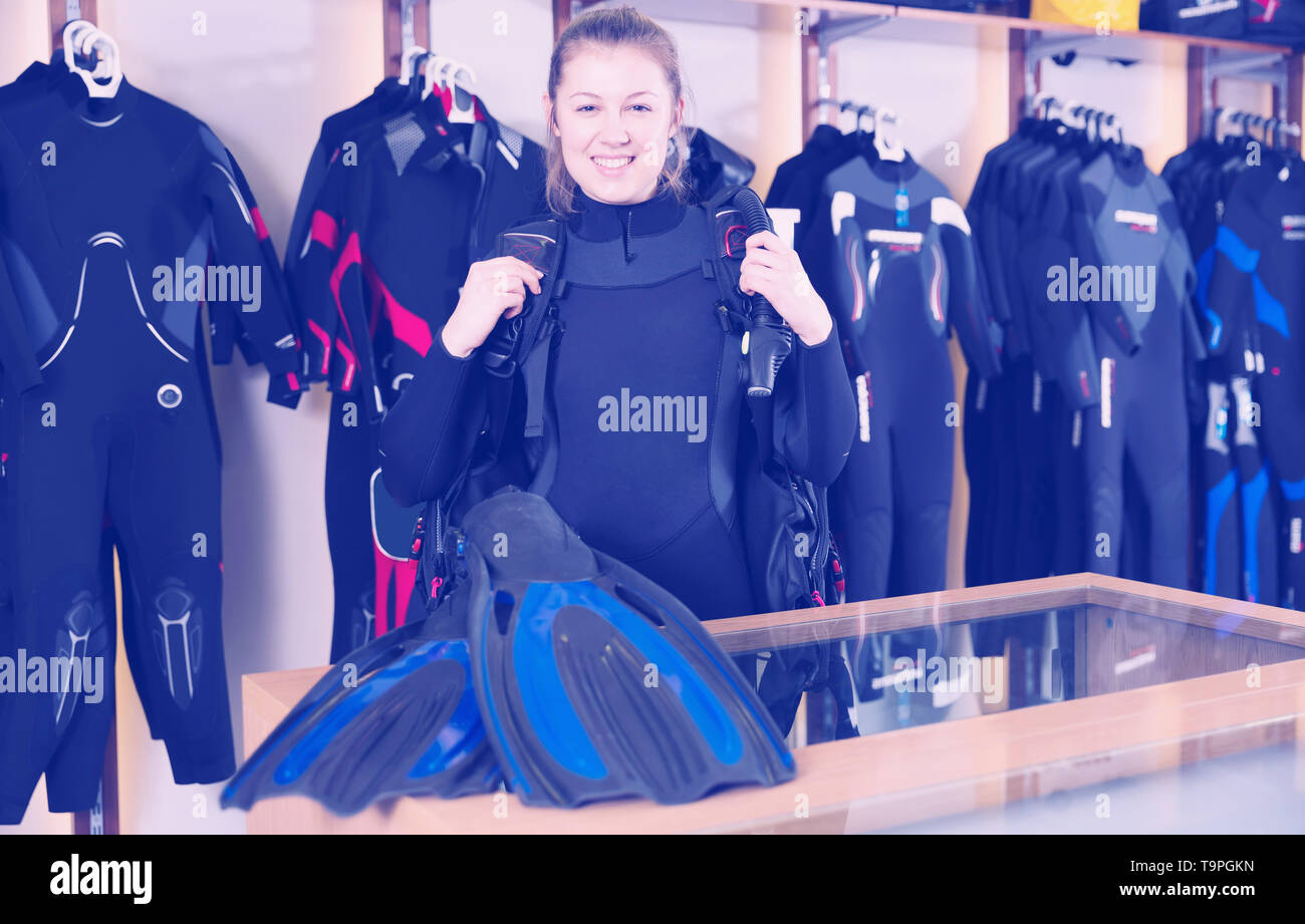 girl is standing in full set of modern diving equipment in the store. - Stock Image