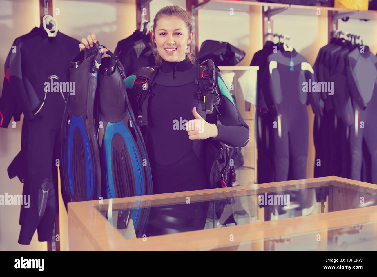 Sporty cheerful positive  woman is satisfied of full set diving equipment in the diving store. - Stock Image