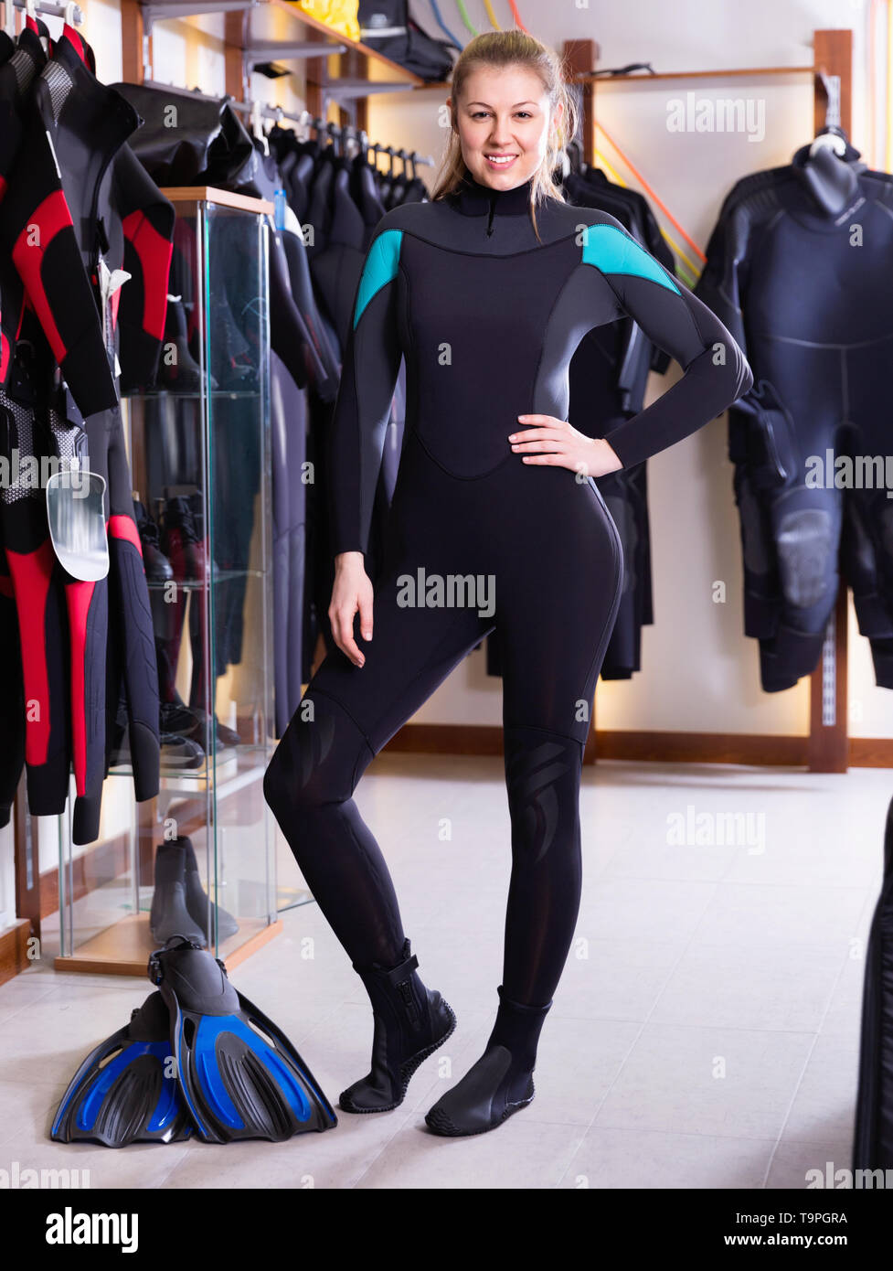 Sporty cheerful  smiling woman is posing in diving costume in the diving store. - Stock Image