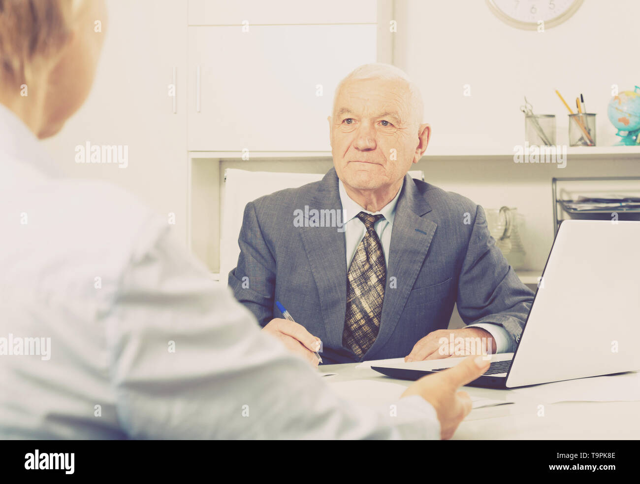 Smiling man manager talking with important client in his office - Stock Image