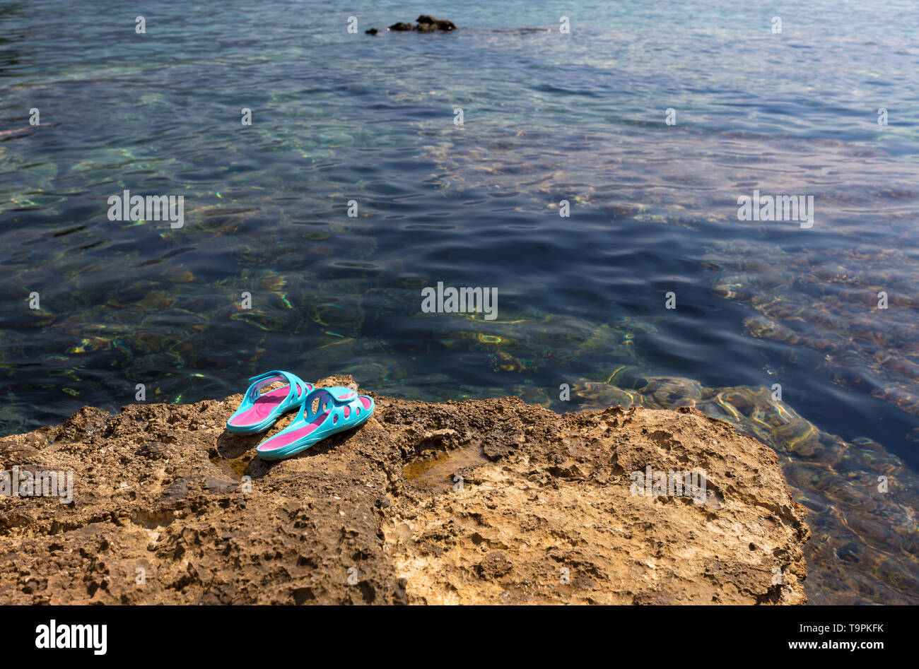 Beach women's slippers of bright turquoise color lie on a sea stone near the transparent waters of the Adriatic Sea - Stock Image