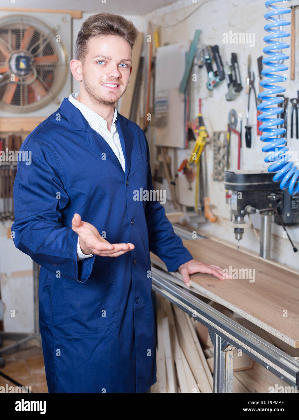 Smiling woodworker practising his skills with milling cutter at workshop - Stock Image