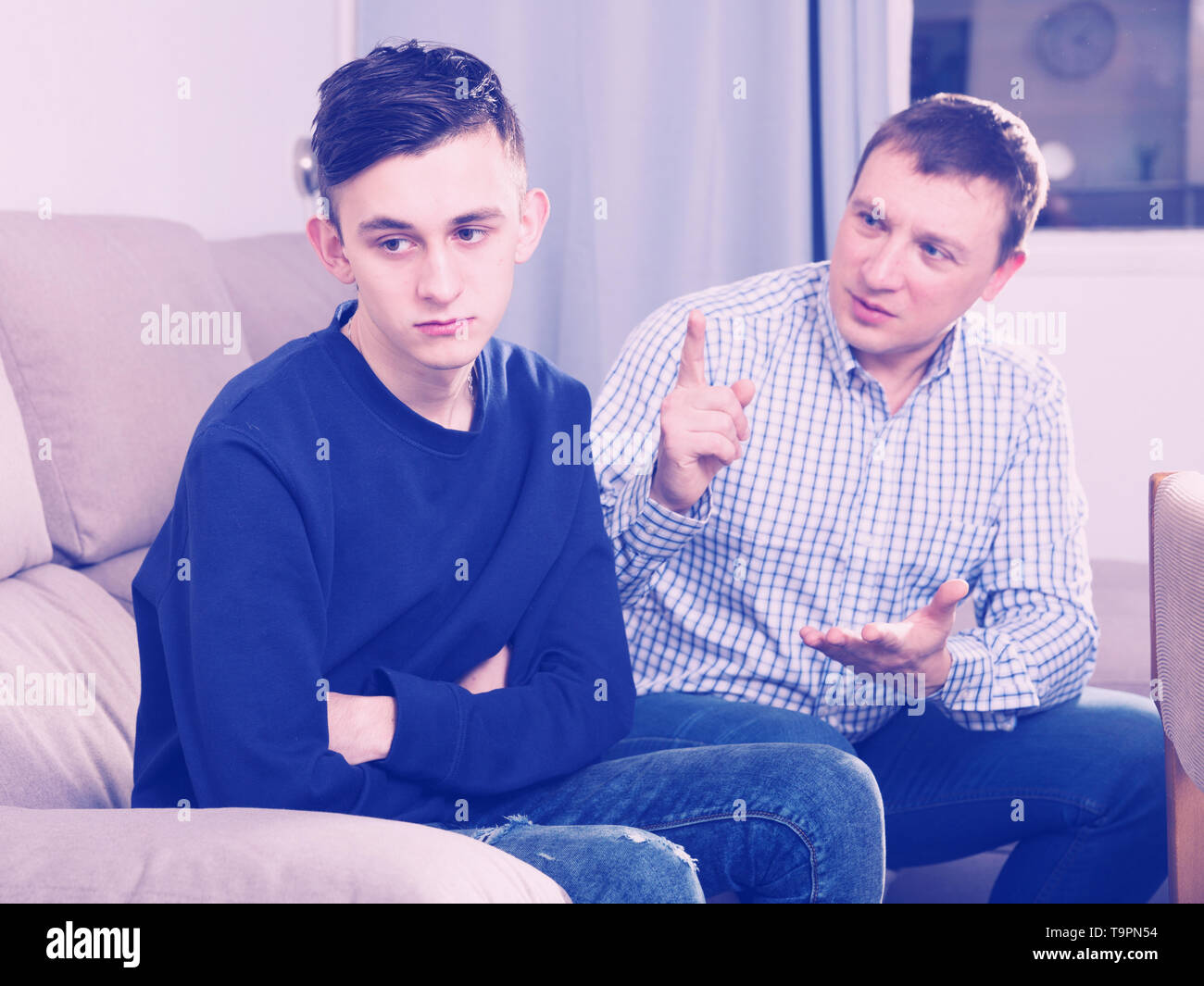 Father is wanting talking with his adult son after conflict at the home. Stock Photo
