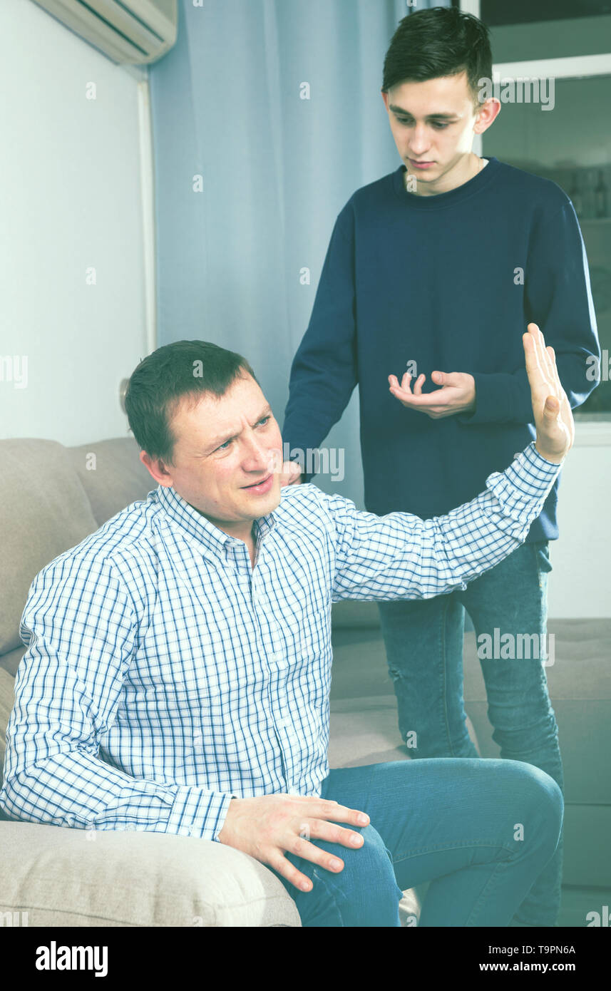 Guy is asking forgiveness from his father after conflict at the home. - Stock Image