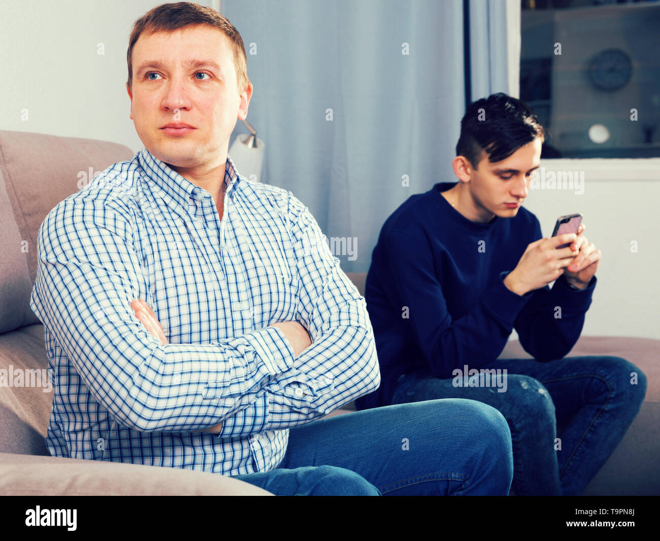 Man with his adult son are conflicting and boy playing with phone at the home. - Stock Image