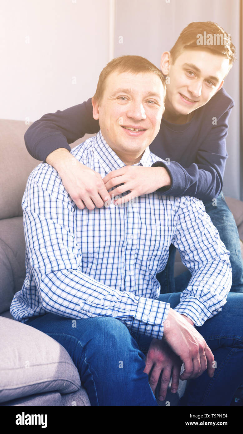 Man with his adult son are posing together at the home. Stock Photo