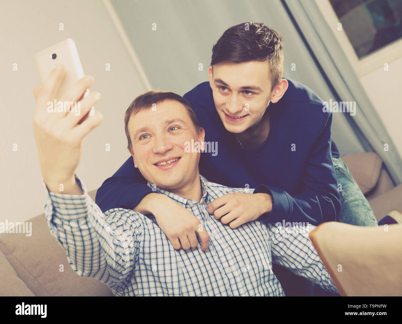 Guy with his father are resting and taking selfie by phone at the home. - Stock Image