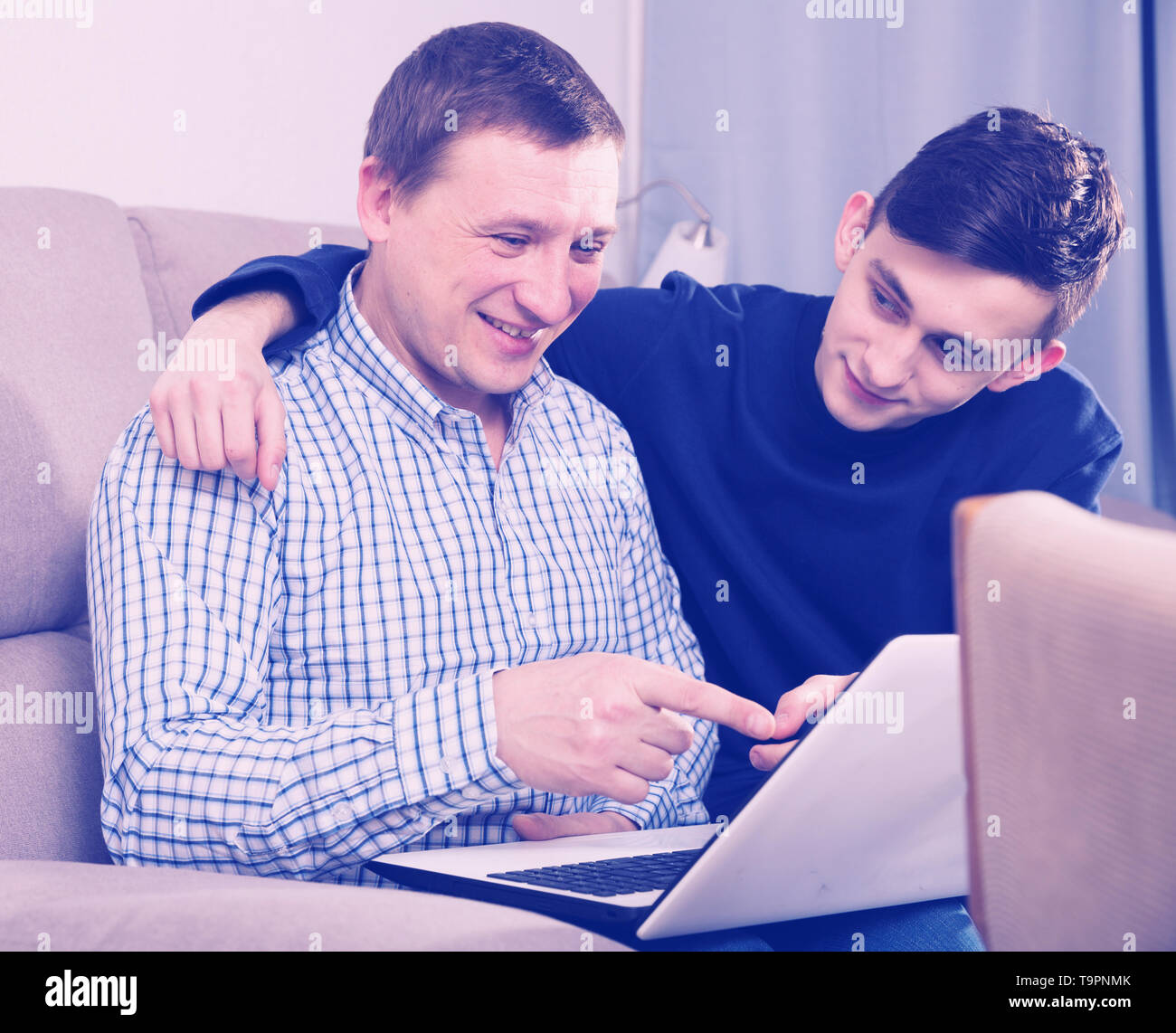 Man with his adult son are playing on laptop together at the home. - Stock Image