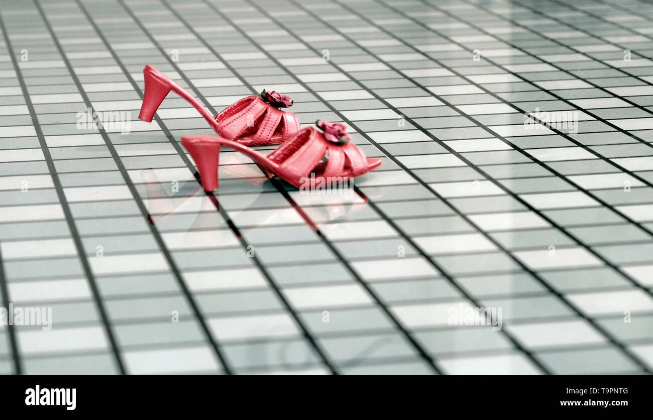 Red womans dancing shoes on a glass checkerboard plate. A fairy tale in themepark the efteling Duiksehoef, Kaatsheuvel, Netherlands - Stock Image
