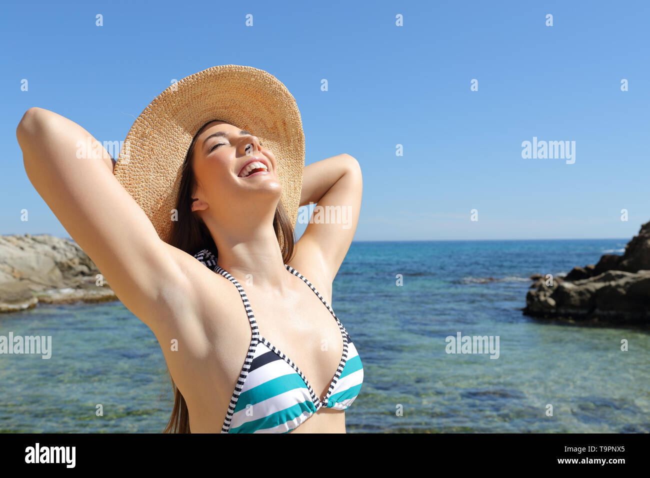Satisfied tourist enjoying summer vacation and sun on the beach - Stock Image