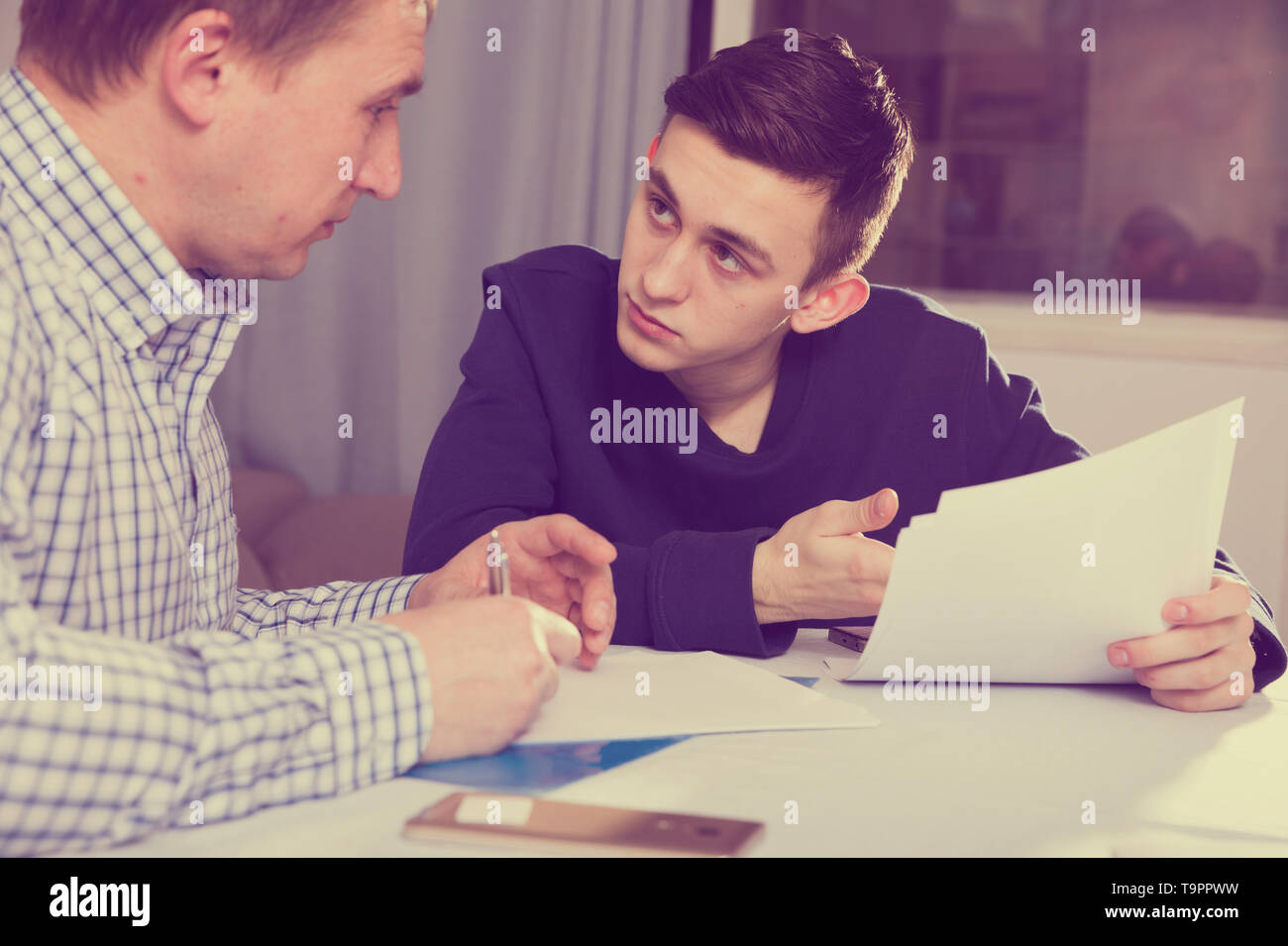 Adult male with his anxious son are looking in documents about studies at the home. - Stock Image
