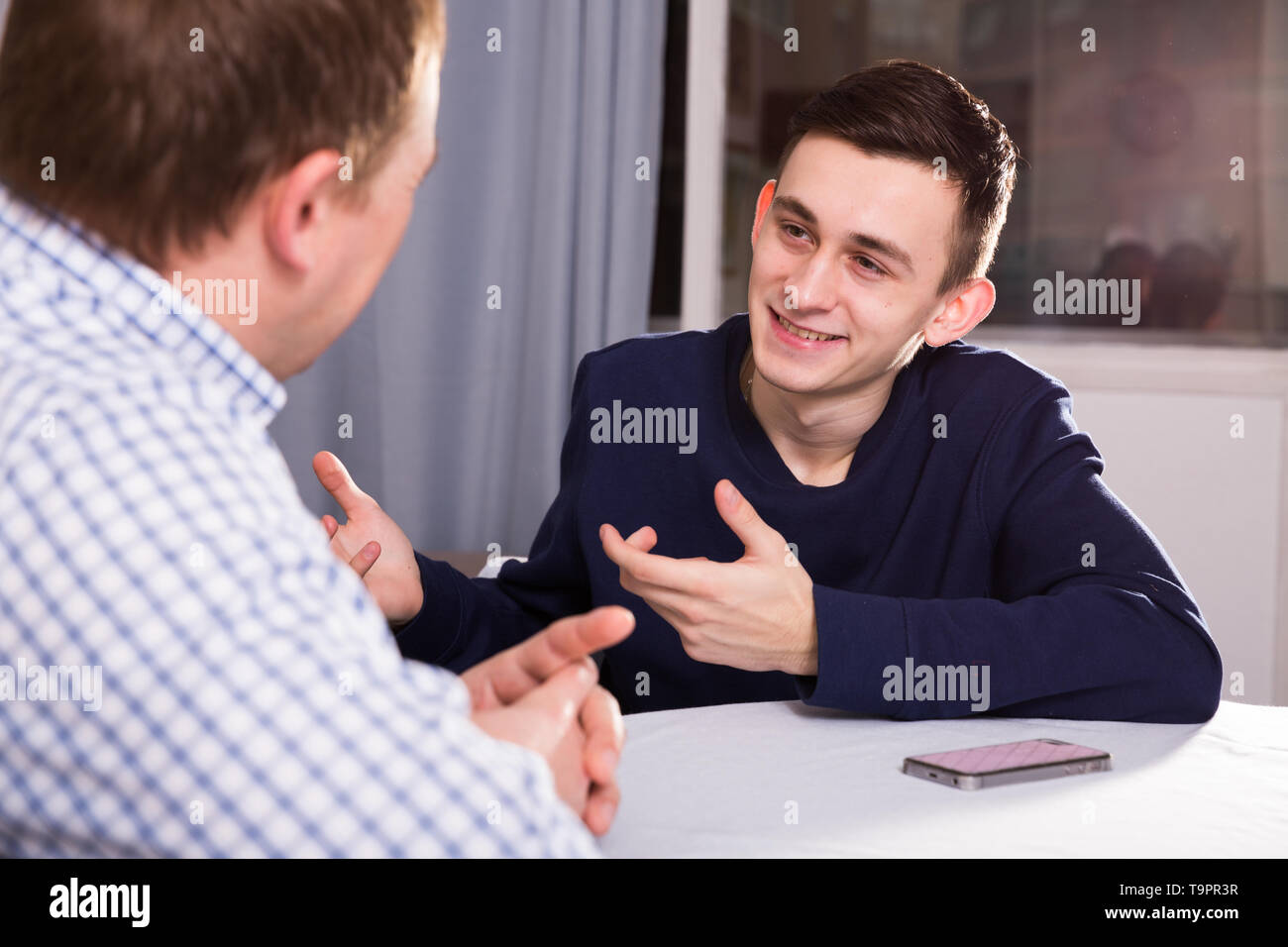 Man with his adult son are talking about life together at the home. - Stock Image