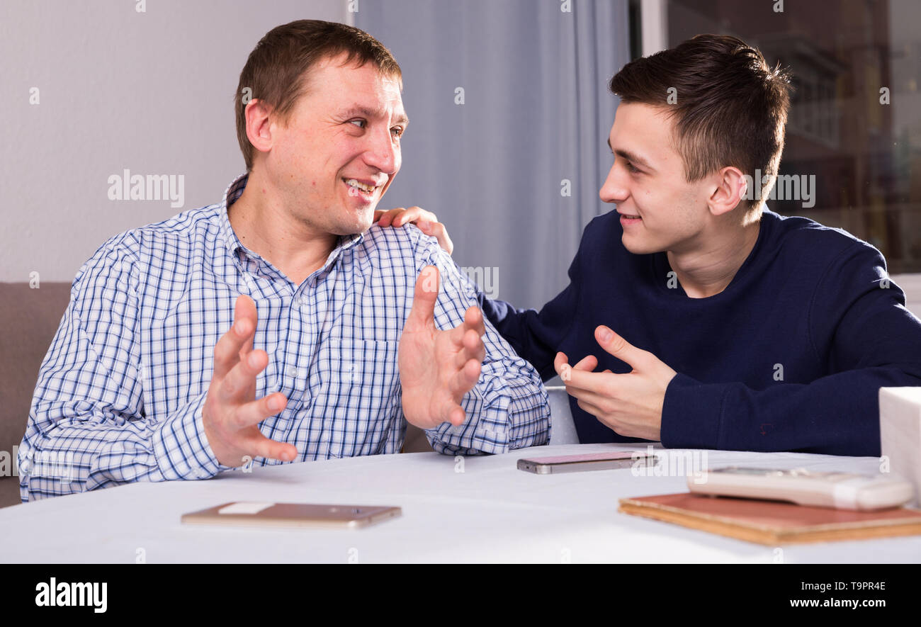Guy with his father are resting and talking about teenage life at the home. Stock Photo