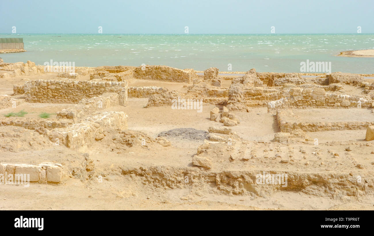 Archaeological excavations of an old fort and the Arabian gulf in the background, Qal'at al-Bahrain - Stock Image
