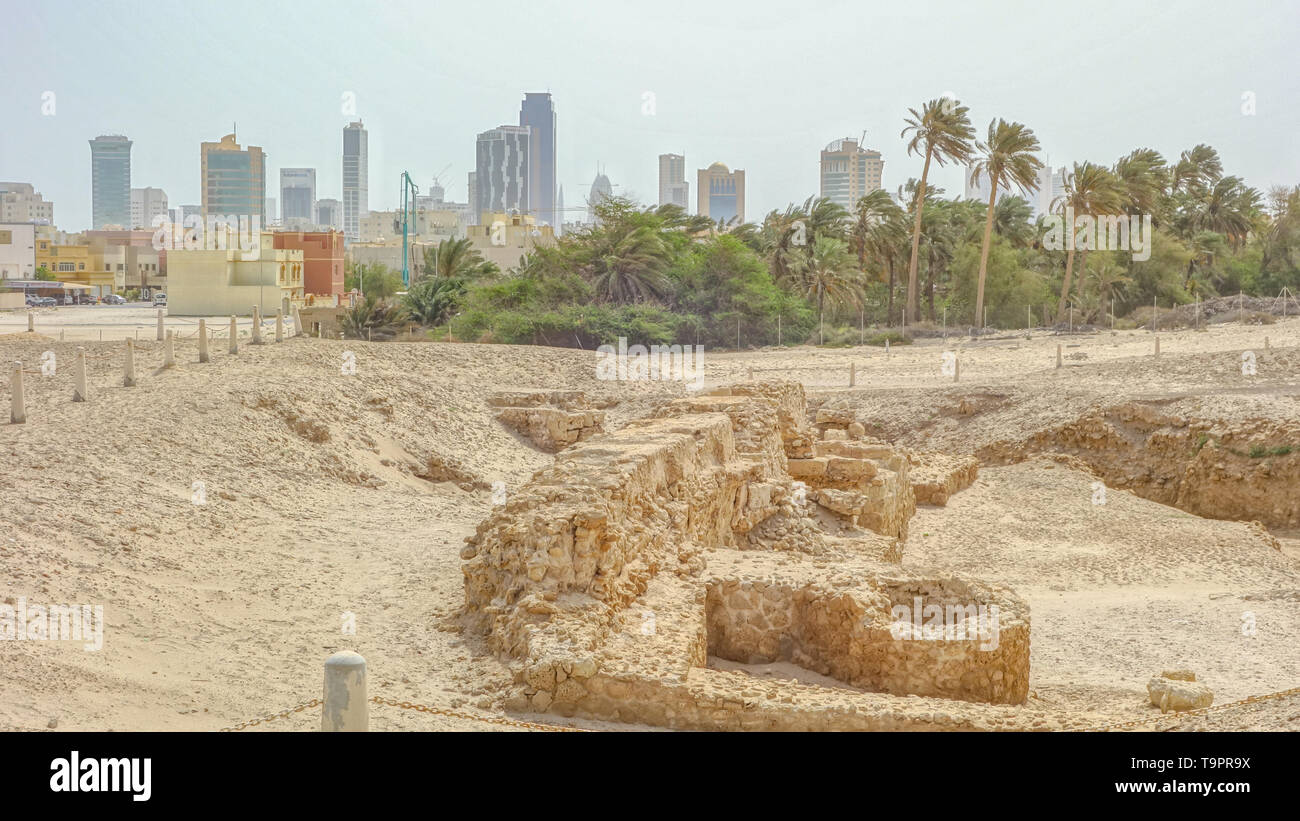 Archaeological excavations of an old fort and Manama skyline in the background, Qal'at al-Bahrain - Stock Image