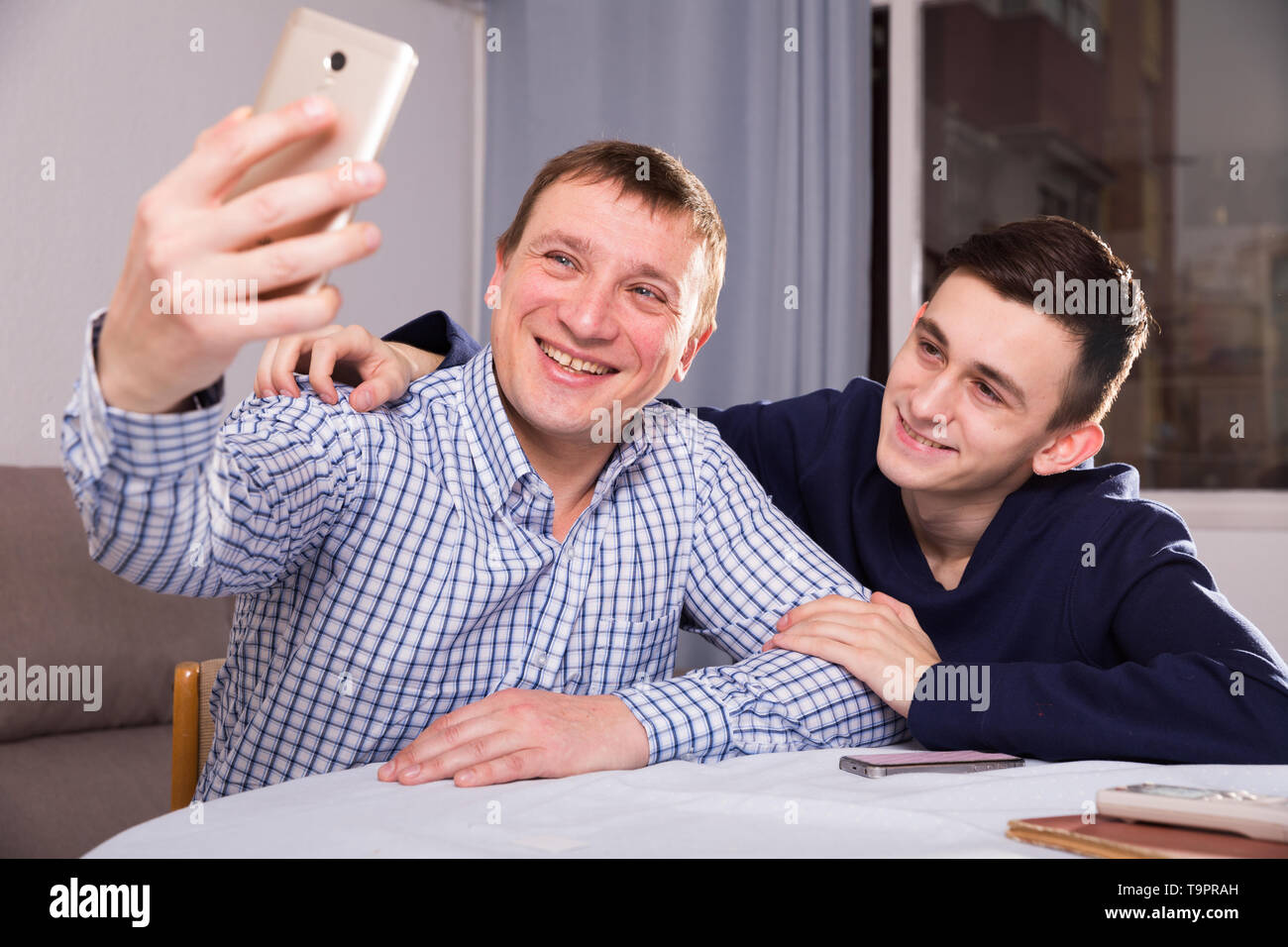 Man with his adult son are taking selfie together at the home. - Stock Image