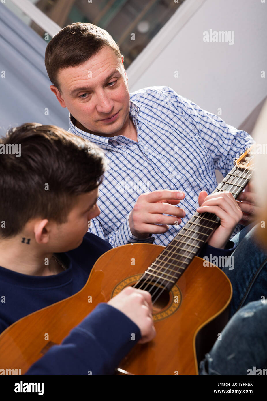 Man with his adult son are playing on guitar together at the home. - Stock Image