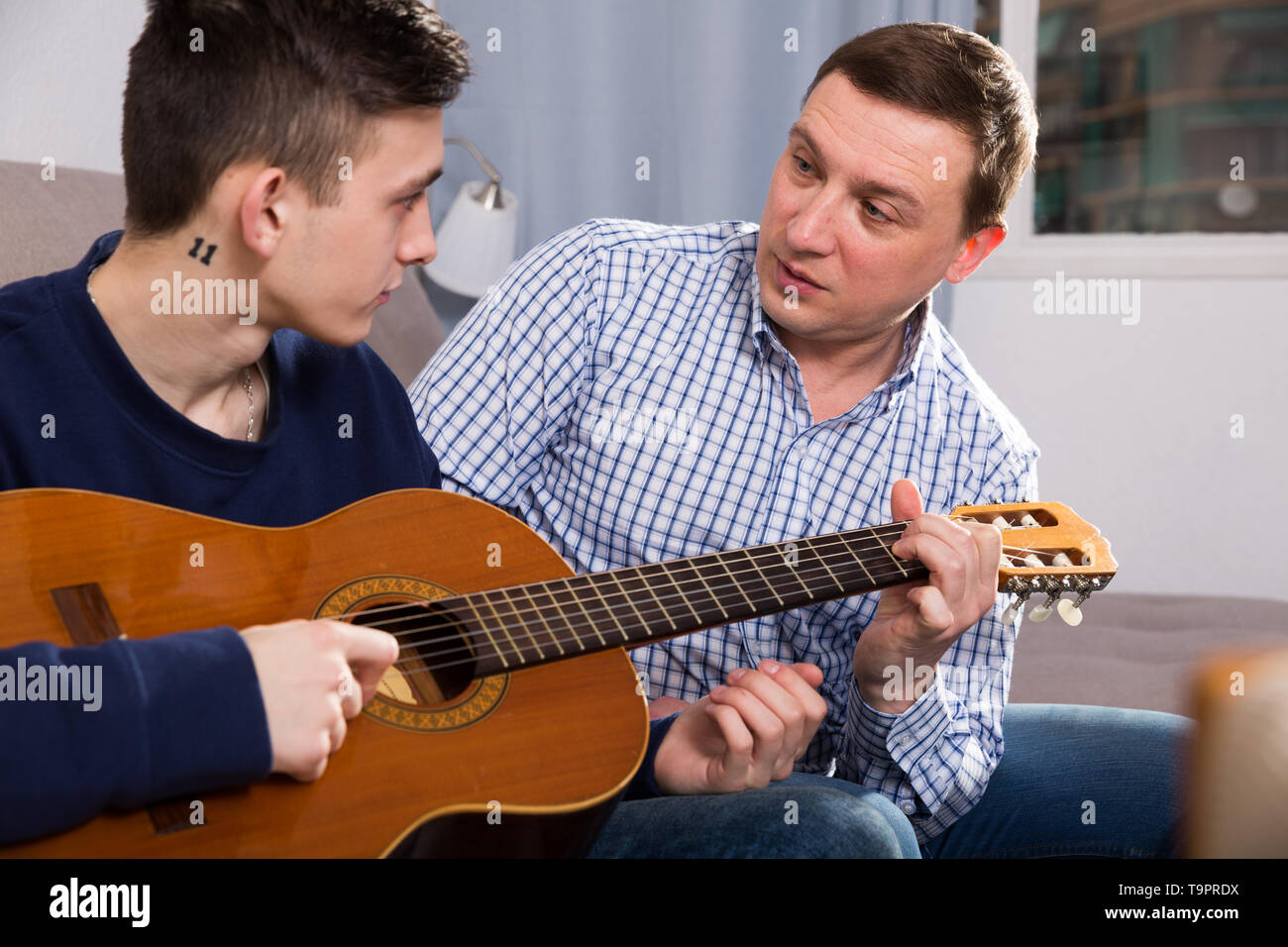 Guy with his father are resting and playing on guitar at the home. Stock Photo