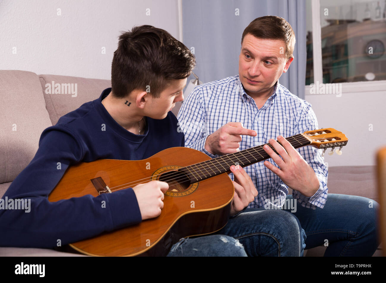 Man with his adult son are playing on guitar together at the home. Stock Photo