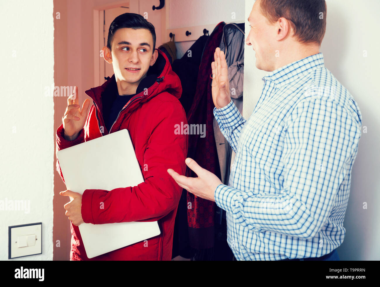 Adult male with his son are saying goodbye before school at the home. - Stock Image
