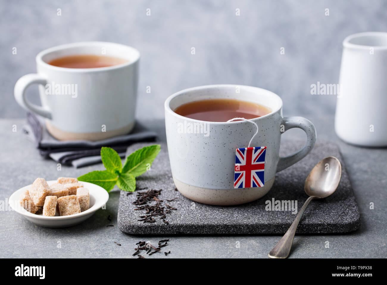 Tea in mugs with British flag tea bag label. Grey background. Close up. - Stock Image