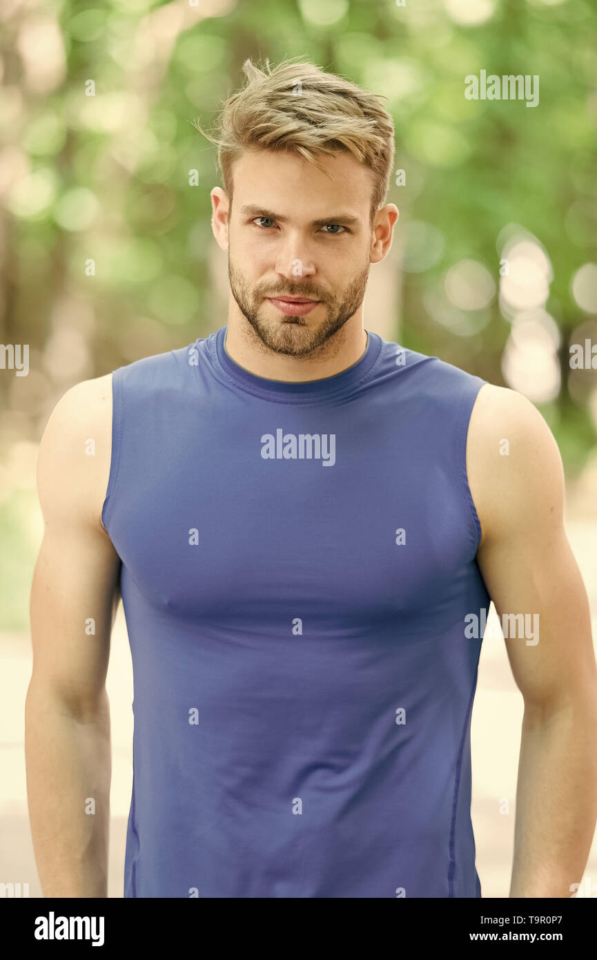 Proud to be strong. Man sporty outfit looks confident outdoors nature background. Guy bearded muscular body proud of his shape. Sportsman enjoy his mu - Stock Image