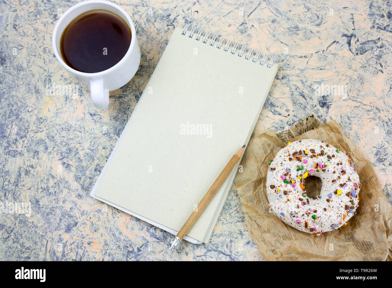 top view mock up notebook with   blank  white paper sheet ,coffee cup and donut - Stock Image