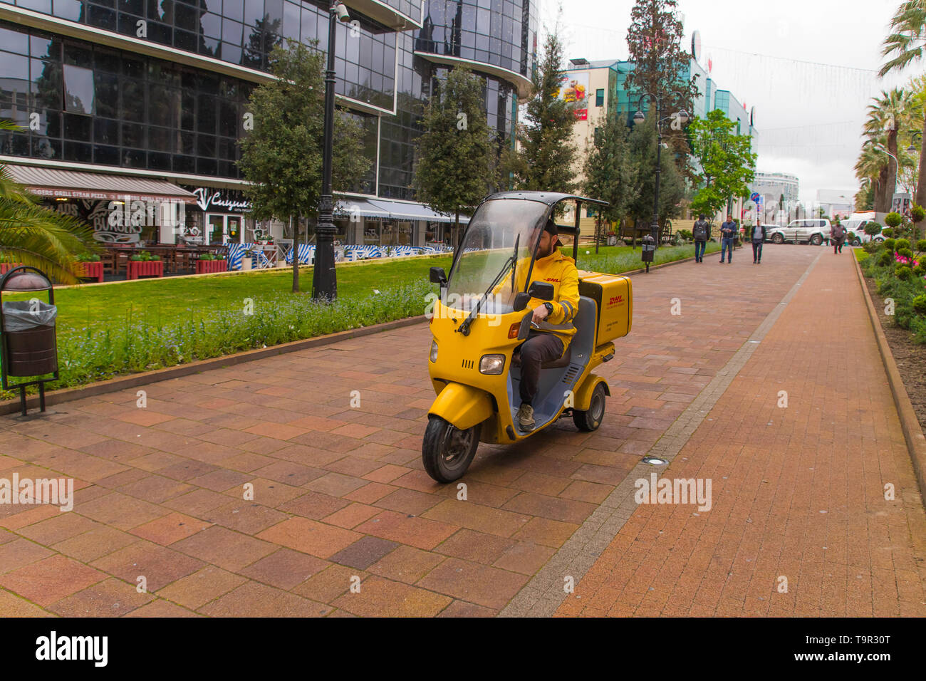 SOCHI,RUSSIA, 18 APRIL 2019 - delivery of consignments on motorbike, motorcyclist rides with delivery in the large yellow box on street - Stock Image