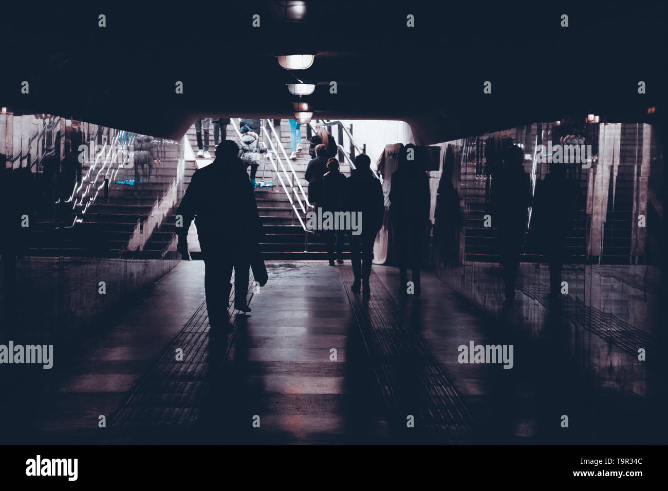 silhouettes of people in an underground pedestrian crossing - Stock Image