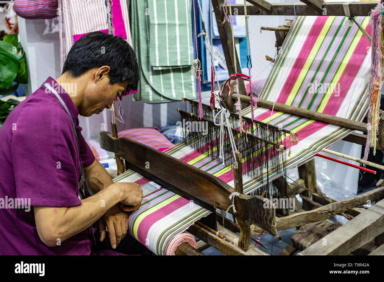 Man using smartphone on antique weaving loom - Stock Image