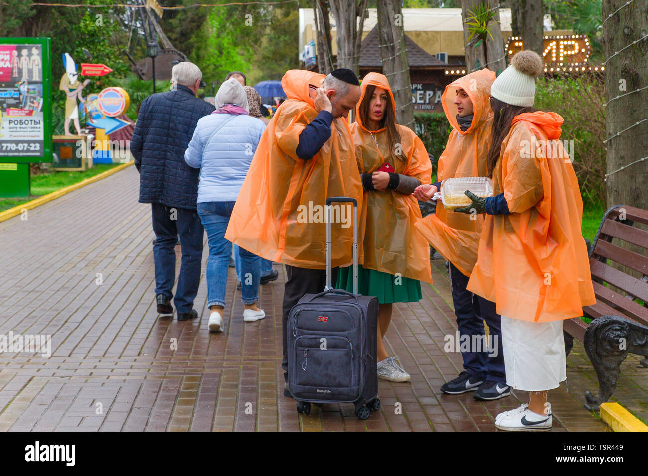 SOCHI,RUSSIA,  21 APRIL 2019 - a group of tourists in the Riviera park dressed in orange raincoats in cloudy weather - Stock Image