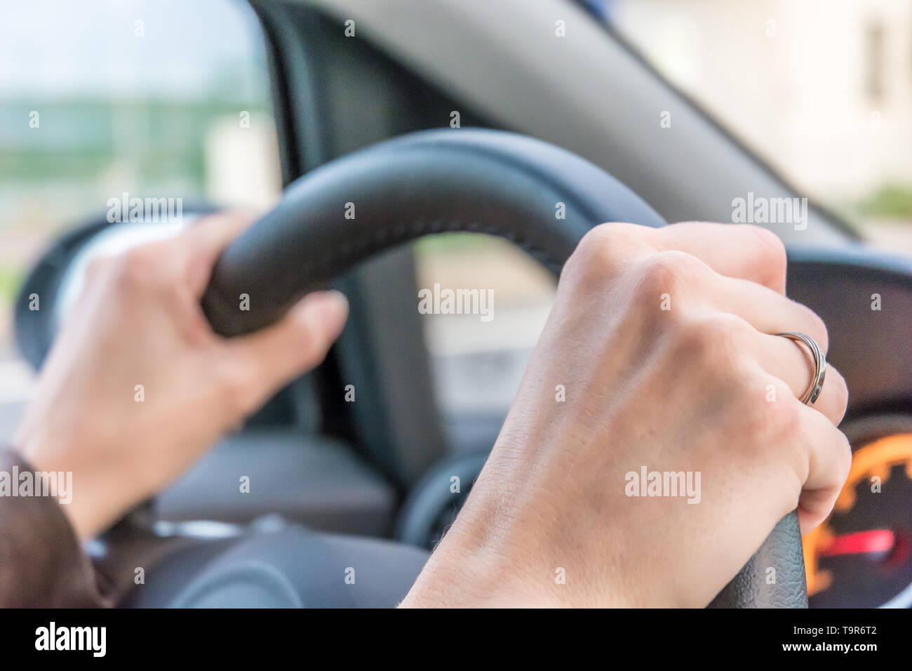 Woman holds the steering wheel tight while driving - Stock Image